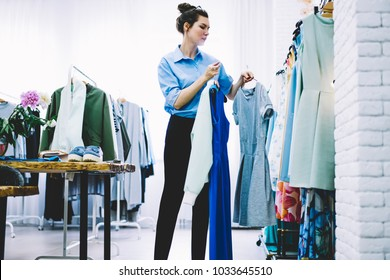 Concentrated young woman with eyeglasses on head working professional stylist in fashionable atelier and choosing trendy clothes for creating cool image holding hangers with textile apparel in hands