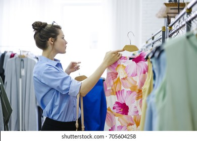 Concentrated young woman with eyeglasses on head working professional stylist in fashionable atelier and choosing trendy clothes.Successful female owner of showroom creating business