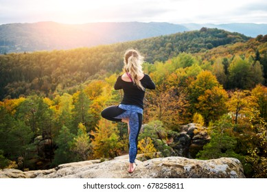 Concentrated young woman is practicing yoga and doing asana Vrikshasana on the top of the mountain in the evening. Beautiful sunset, autumn forests, rocks and hills on the background