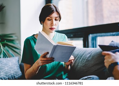 Concentrated young woman reading literature plot in book preparing for upcoming exam and studying at home with modern interior.Pensive hipster girl enjoying bestseller in apartment in leisure time