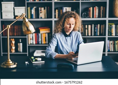 Concentrated young woman sitting at desk in library and working on laptop and phone from home.