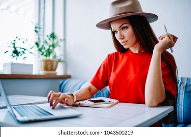 Concentrated young woman in stylish hat reading information on website before making money transaction, hipster girl watching webinar on laptop learning in online courses of design sitting in cafe