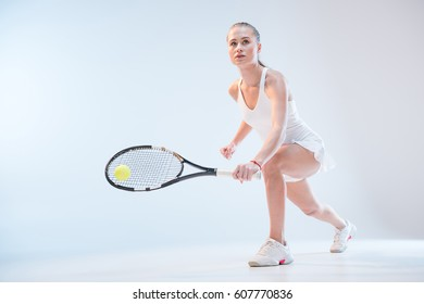 concentrated young woman in tennis uniform with racket and ball playing tennis isolated on white