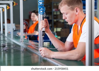 Concentrated young workers on production line, horizontal