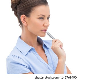 Concentrating businesswoman with pen looking away