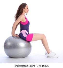 Concentrating on balance exercise, a beautiful young woman in sitting pose on fitness ball. She is wearing bright blue and pink sports clothes and white trainers.