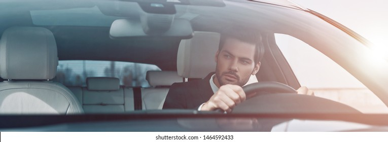 Concentrating on the road. Handsome young man in full suit looking straight while driving a car
