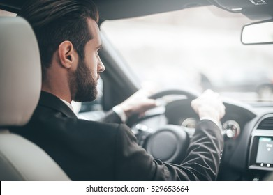 Concentrating on the road. Rear view of young handsome man looking straight while driving a car