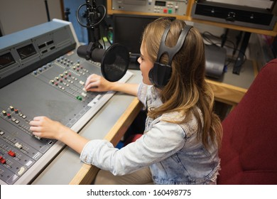 Concentrating pretty radio host moderating sitting in studio at college