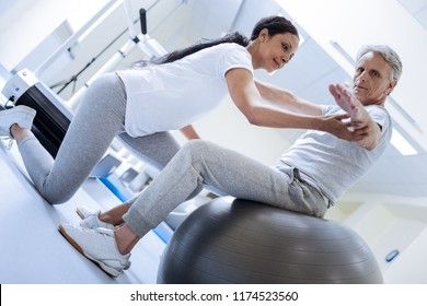 Concentration. Calm attentive professional trainer being in a rehabilitation center and helping a weak aged man on a big fitball to raise his hands