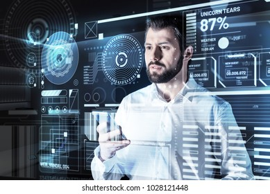 Concentration. Clever experienced qualified programmer feeling concentrated while standing in front of a modern transparent futuristic screen and holding a tiny smartphone in his hand