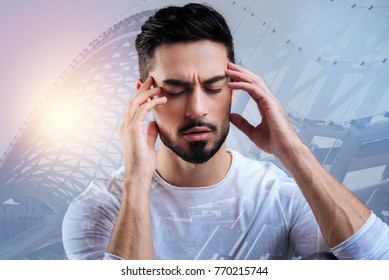 Concentration. Smart responsible attentive student closing his eyes and touching the forehead while concentrating at the difficult important examination