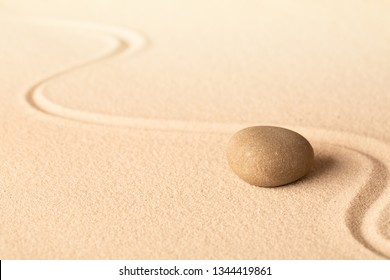 Concentration trough focus on a zen meditation stone. Round rock in sand texture background. Concept for yoga or spa welness treatment.
