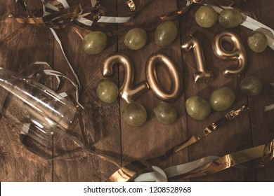 Concept 2019. Photograph of 2019 golden numbers, with grapes and decorations for the end of the year celebration.