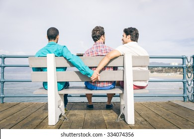 Concept about cheating in a relationship. Gay couple and a third lover on a bench