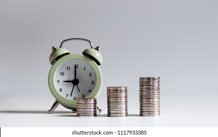 A concept about the relationship between time and money. An alarm clock and three stack of coins.