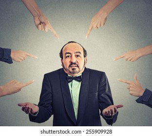 Concept of accusation of guilty arrogant businessman. Middle aged man judged by different people many women fingers point at him. Guy shrugs shoulders