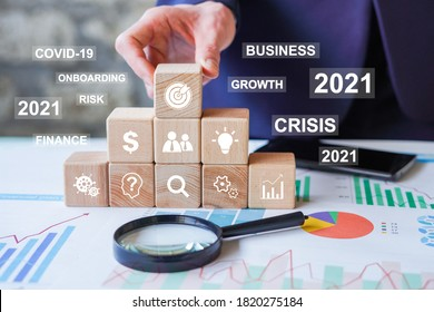 Concept of achieving business goal in 2021 year covid-19. Businessman hand arranging wood block stacking with business growth in 2021 year, business onboarding, coronavirus, protect your business.