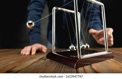 Concept For Action and Reaction in Business With Newton's Cradle with Businessman