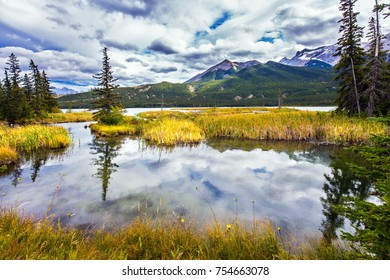 Concept of active and ecological tourism. Magnificent journey through the Rocky Mountains of Canada. The smooth water of the lake reflects the cloudy sky