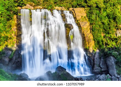 Concept of active and ecological tourism. Marokopa falls at sunset. Exotic journey to the North Island, New Zealand