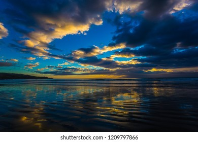 The concept of active and ecotourism. Incredible sunset on the Pacific coast, New Zealand. The darkened clouds are reflected in the gentle ripples of the surf