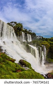 The concept of active and exotic tourism. The most famous waterfalls in the world - Iguazu. The waterfalls erupts clouds of water spray