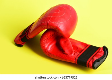 Concept of active lifestyle and fighting with pair of red gloves for thai boxing isolated on yellow background