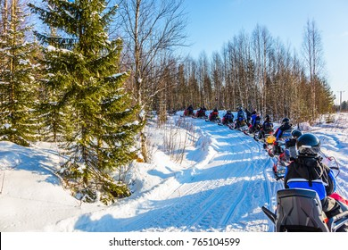 Concept of active winter tourism. Snowmobiling. Tourist train from snowmobiles moves along the ice of a frozen river