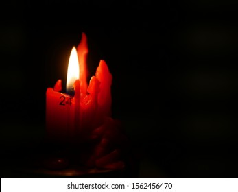 Concept of advent on day 24 (CHristmas Eve) shown by red advent candle with numbered advent days down the side, lit with flame in dark room