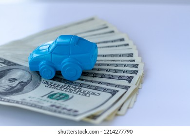 Concept for advertising loan, collateral, pawnshop, car rental. Money and cars. An idea to illustrate buying a car in installments or as collateral. Toy car and real dollar bills.