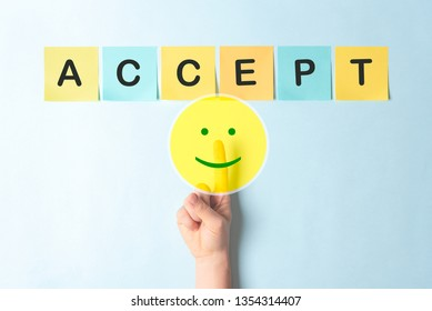 Concept of agree with your opinion, with finger touching a button with a happy smiling face. The word ACCEPT is written on multicolored notes with a blue background.