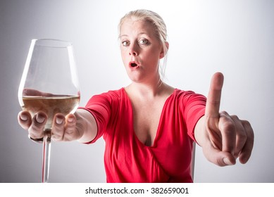 A concept of alcoholism. A young woman in red dress saying no to alcoholic beverage.