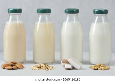 Concept alternative to cow's milk.  Bottles with coconut, oat, soy and almond milk.  Next to the bottles are pieces of coconut, almonds, oatmeal and soybeans.  Light background.  Close-up.