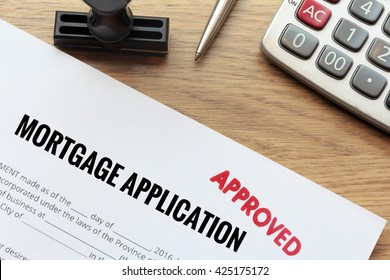 Concept of Approved mortgage application form lay down on wooden desk with rubber stamp and calculator.