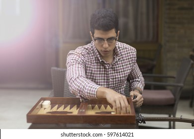 concept of Arabian Arabic elegant attractive young man model playing backgammon and looking to the camera in a cafe in cairo, egypt at middle east, Africa