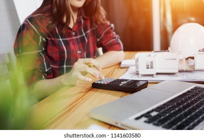 Concept architects,  architect woman using calculator for accounting and analyzing building structure On the desk with a blueprint in the office.