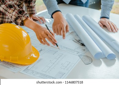 Concept architects, Engineer holding pen pointing equipment architects On the desk with a blueprint in the office.Selective Focus