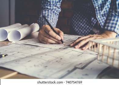 Concept architects, engineer holding pen pointing equipment architects On the desk with a blueprint in the office, Vintage, Sunset light.Selective Focus - Shutterstock ID 740754769