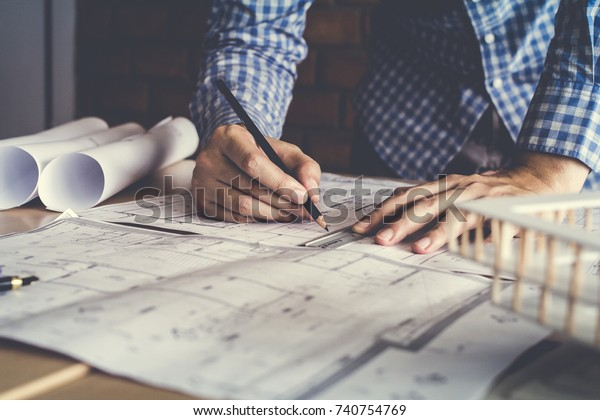 Concept architects, engineer holding pen pointing equipment architects On the desk with a blueprint in the office, Vintage, Sunset light.Selective Focus