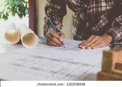 Concept architects, Engineer using pencil drawing equipment architects with wooden model On the desk with a blueprint in the office