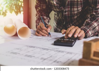 Concept architects, Hand of asian young man engineer using calculator for calculation number of structural materials architects On the desk with a blueprint in the office.