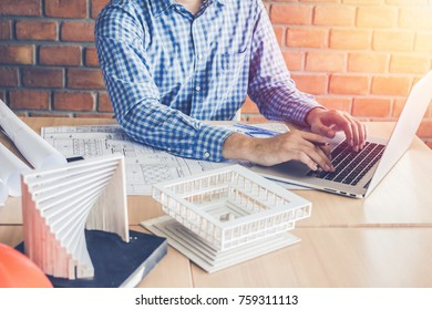 Concept architects,engineer using working on laptop with  blueprint and model in the office, Vintage, Sunset ligth.Selective Focus