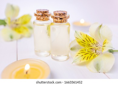 The concept of aromatherapy, spa. Bottles with floral essential oil on a white wooden background. Nearby is a yellow flower, candles. Cozy still life in bright colors.