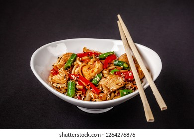 Concept of Asian cuisine. Wheat noodles from durum flour with vegetables and chicken. Carrots, bell peppers, green beans, white and black sesame. Japanese or Chinese dish.