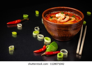 concept of Asian traditional cuisine. Japanese or Chinese miso soup with seafood, with shrimp and leek. next to Chinese sticks on a black background. Copy space