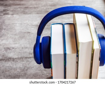 Concept of audiobook. Books on the table with headphones put on them