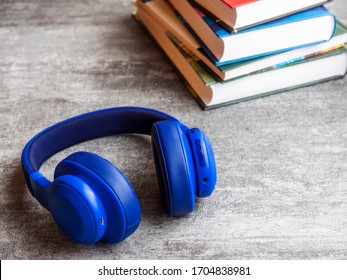 Concept of audiobook. Books on the table with headphones next to them. Side view