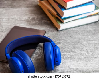 Concept of audiobook. Books on the table with headphones and tablet computer next to them. Side view