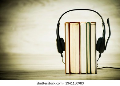 Concept of audiobooks, headphones with microphone and books on vintage background